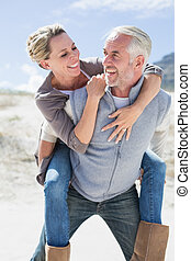 Laughing couple smiling at each other on the beach on a...