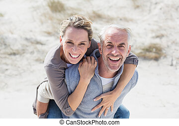 Laughing couple smiling at camera on the beach on a bright...