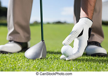 Golfer placing golf ball on tee on a sunny day at the golf...
