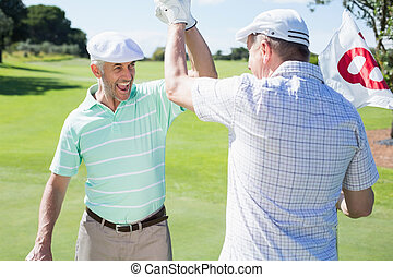 Golfing friends high fiving on the eighteenth hole on a...