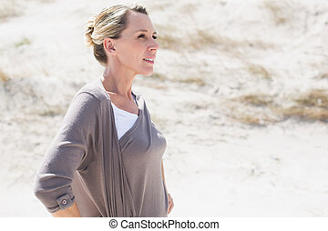 Thinking blonde woman standing on the beach on a bright but...