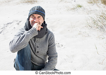 Attractive man thinking on the beach in hat and scarf on a...