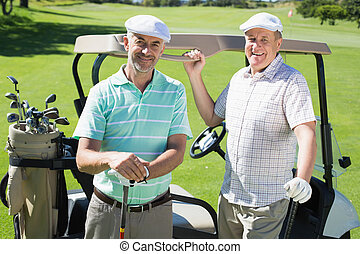 Golfing friends standing beside their buggy smiling at...