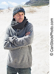Attractive man shivering on the beach in hat and scarf on a...