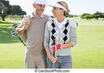 Golfing couple smiling at each other on the putting green on...