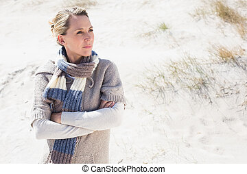 Attractive blonde standing on the beach in woolen scarf on a...