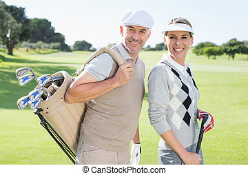 Golfing couple smiling at camera on the putting green on a...