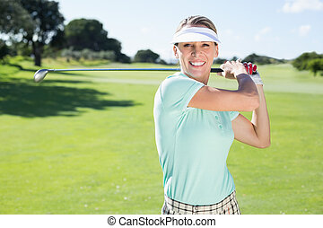 Lady golfer teeing off and smiling at camera on a sunny day...