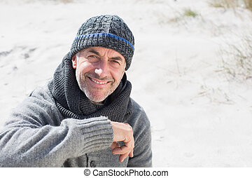 Attractive man smiling on the beach in hat and scarf on a...