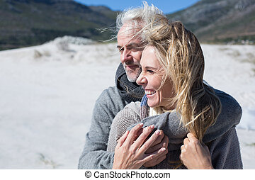 Carefree couple hugging on the beach in warm clothing on a...