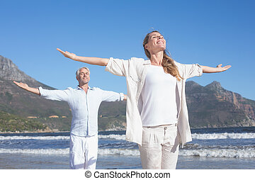 Happy couple standing with arms outstretched at the beach on...
