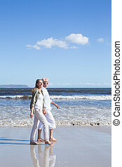 Happy couple strolling barefoot on the beach