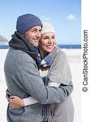 Attractive couple hugging on the beach in warm clothing on a...