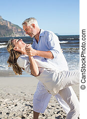 Happy couple dancing on the beach together on a sunny day