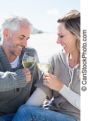 Couple enjoying white wine on picnic at the beach smiling at...