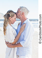 Man kissing his partner on the forehead at the beach on a...