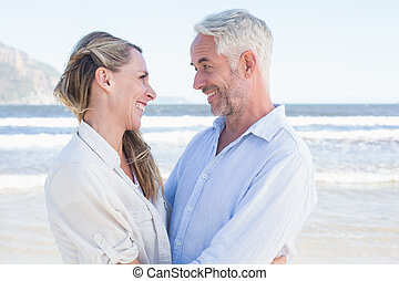 Happy couple hugging on the beach looking at each other