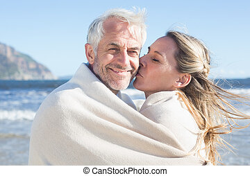 Smiling couple wrapped up in blanket on the beach on a sunny...