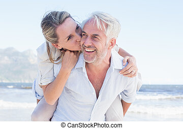 Man giving his smiling wife a piggy back at the beach on a...