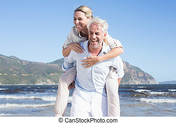 Man giving his laughing wife a piggy back at the beach on a...