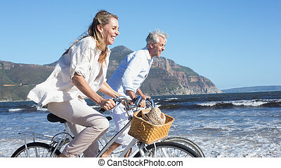 Smiling couple riding their bikes on the beach on a sunny...