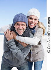 Attractive couple hugging and smiling at camera on the beach...