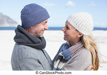 Attractive couple smiling at each other on the beach in warm...