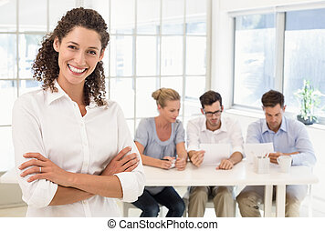 Casual businesswoman smiling at camera with team behind her