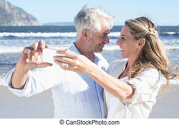 Married couple at the beach together taking a selfie on a...