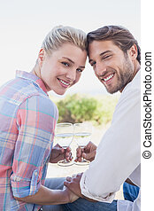 Happy couple smiling at camera holding wine glasses