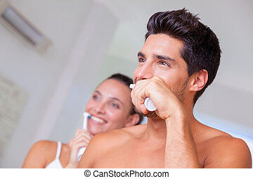 Attractive couple brushing their teeth in the morning