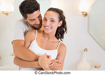 Attractive couple hugging in their pajamas at home in...