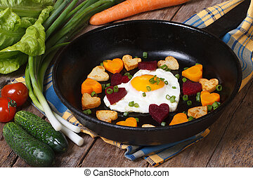 Hearts of carrots, potatoes, beets and eggs in a frying pan...