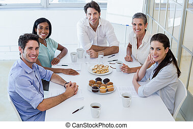 Casual business team having a meeting smiling at camera in...