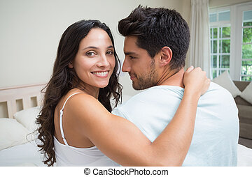 Attractive couple sitting on bed