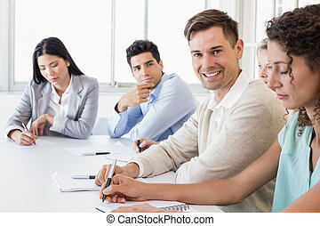 Casual businessman smiling at camera during meeting in the...