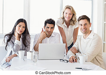 Casual business team having a meeting using laptop in the...