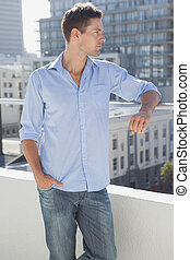 Handsome man looking over his balcony on a sunny day