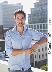 Handsome man smiling at camera on his balcony on a sunny day