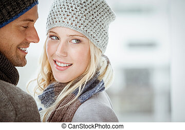 Couple in warm clothing hugging on a sunny day in the city