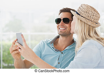 Cute couple sitting in cafe taking a selfie on a sunny day...