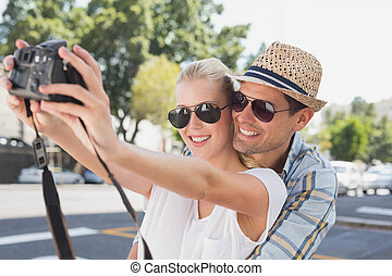 Young hip couple taking a selfie on a sunny day in the city
