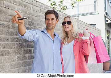 Stylish young couple walking with shopping bags on a sunny...