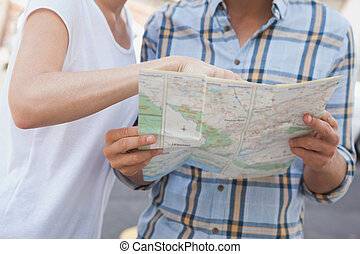 Young tourist couple looking at map