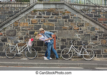 Hip young couple dancing by brick wall with their bikes on a...