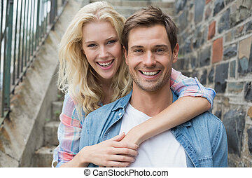 Hip young couple sitting on steps smiling at camera on a...