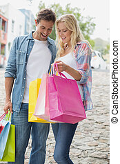 Hip young couple looking at their shopping bags