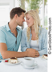 Hip young couple having desert and coffee together on the...
