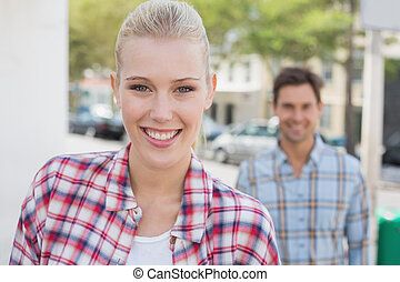Young hip couple smiling at camera