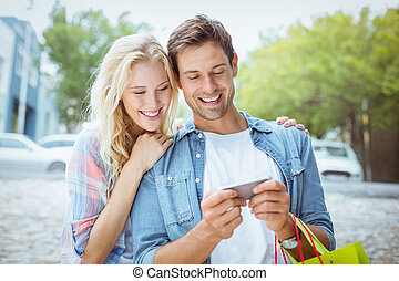 Hip young couple looking at smartphone on shopping trip on a...